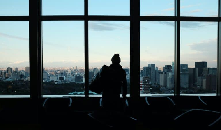 silhouette of person looking to glass window