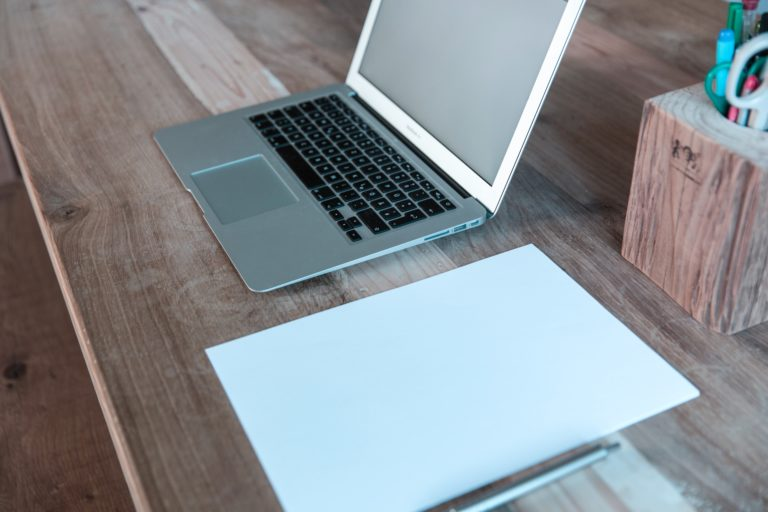 MacBook Pro on brown wooden table near pen organizer