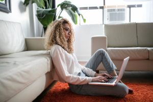 woman sitting on floor and leaning on couch using laptop