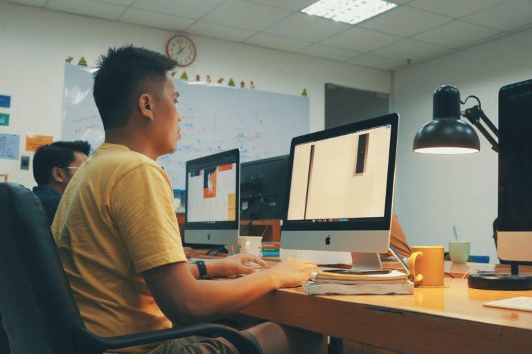 man using Apple desktop inside room beside man