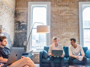 three men using MacBooks
