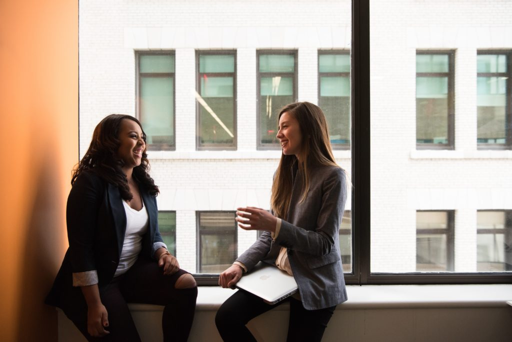two woman sitting by the window laughing
