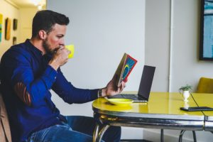 man drinking on yellow cup while reading book